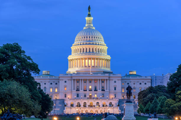Summer Night at Capitol Hill - A dusk view of west-side of the U.S. Capitol Building, as a small crowd gathering around a summer concert at front, Washington, D.C., USA. stock photo