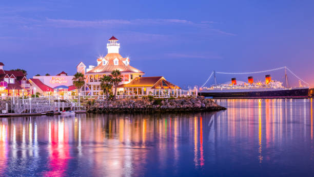 Summer Nights at Rainbow Harbor Long Beach, CA, USA - July 23th 2019: A summer evening overlooking the Parkers Lighthouse restaurant with the Queen Mary in the background. long beach california stock pictures, royalty-free photos & images