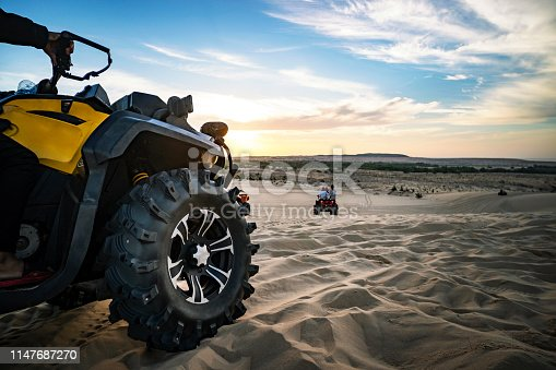 Summer offroad adventure on atv in sand quarry. Entertainment of tourists in the desert in MUI ne in Vietnam. Off-road ATV wheel close-up