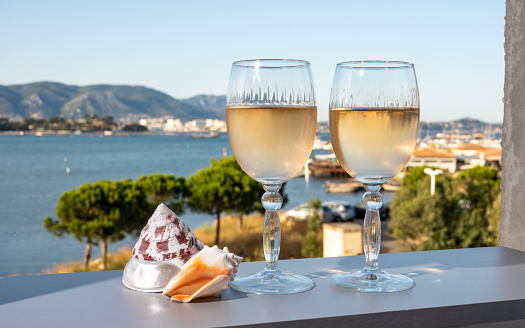 Summer on French Riviera, drinking of cold white or rose gris wine from Cotes de Provence on outdoor terrase with view on harbour of Toulon, Var, France and sea shells