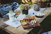 istock summer outdoor garden table setting with flowers, candles, white wine, cheese and fruits 1125372808