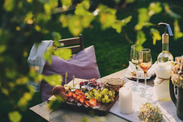 summer outdoor party table with white wine, cheese and ham plate with fruits. Garden festive table. stock photo