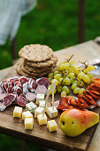 istock summer outdoor table with cheese and ham plate on cutting board with fruits and wine in glasses. Romantic dinner outdoor 1125373405