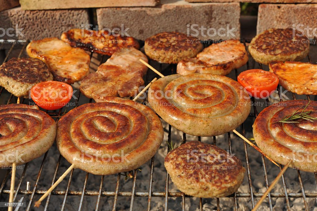 Summer outside cooking on a barbecue, sausages, pork, burgers, rosemary royalty-free stock photo