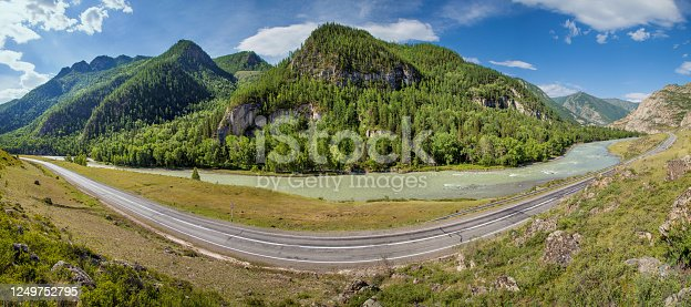 Summer panoramic view. Asphalt road passes through the gorge along the river, Chuiski tract, Altay. Travels in Russia.