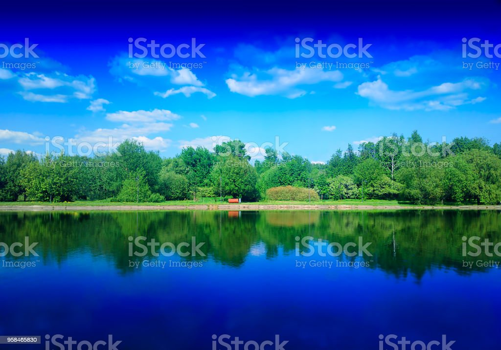 Summer park on river with dramatic reflections background stock photo