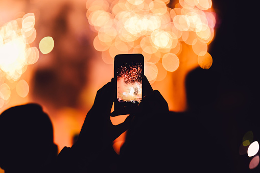 People on party recording firework display with smartphone