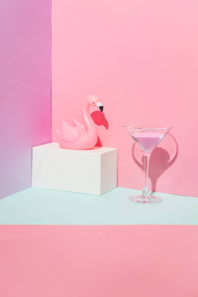 Summer party composition on a geometric background with pink flamingo and glass of cocktail. Beach or swimming pool concept stock photo