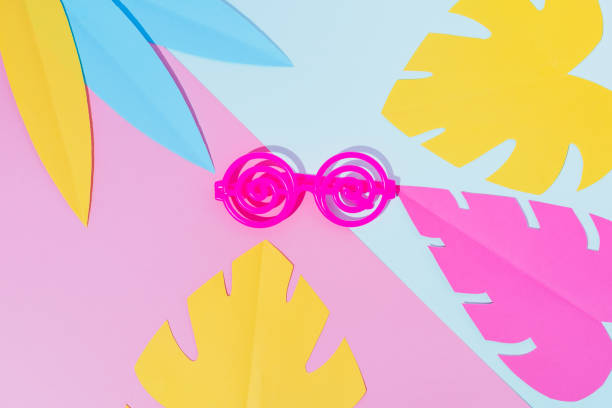 Summer party composition on a geometric background with plastic twisted sunglasses and tropical palm leaves. Beach or swimming pool concept. Flat lay stock photo