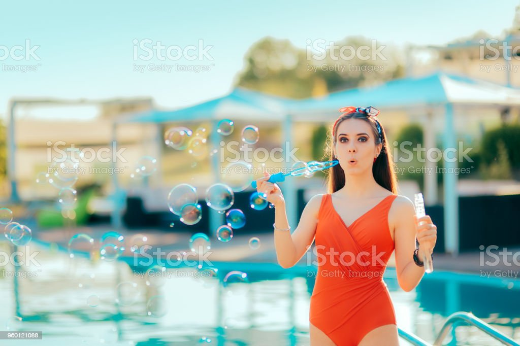 Summer Party Girl Blowing Soap Bubbles by the Pool stock photo