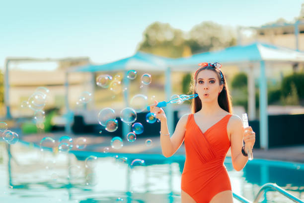 Summer Party Girl Blowing Soap Bubbles by the Pool Woman celebrating 4th of July in outdoor festive event happy 4th of july photos stock pictures, royalty-free photos & images