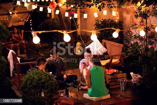 Group of pretty young people have a night party in a backyard