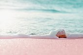 Summer pastel colored background - sandy beach and sea water over small stone