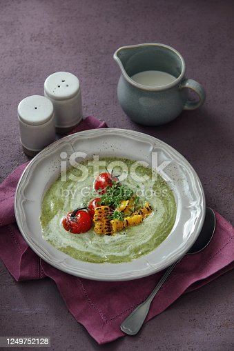 Summer Pea and Watercress Soup with Grilled Tomatoes and Corn. Close-up composition on dark purple background
