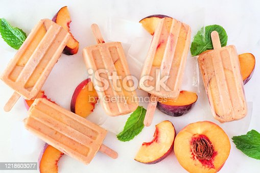 Summer peach yogurt ice pops, top view scattered on a white marble background