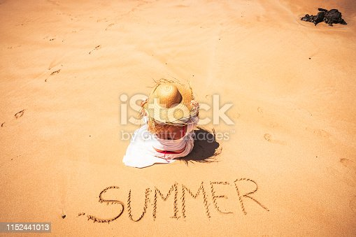 Summer people travel holiday vacation concept with young caucasian beautiful woman sit down at the beach enjoying the sun with the word summer wrote on the sand - resort paradise
