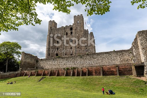 Rochester, England - May 3, 2018 : People picnic outside the old stone defensive walls and high towers of the 12th-century Rochester Castle.