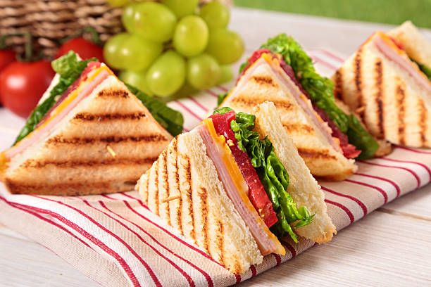summer picnic club sandwich ham and cheese in a row - club sandwich stock photos and pictures