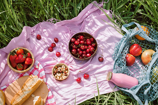 summer picnic on the with cherries in the wooden coconut bowls, fresh bread and glass bottle of juice or smoothie on pink blanket