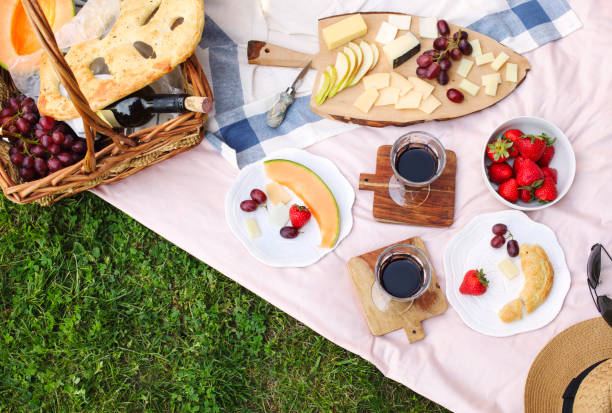 summer picnic with cheese, wine, fruits and bread. picnic at the park. - picnic foto e immagini stock