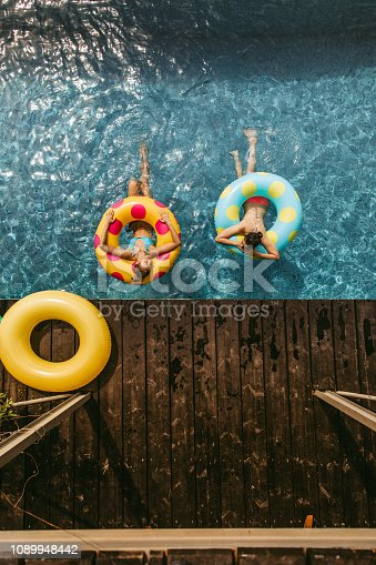 Two girlfriends with inflatable rings in the swimming pool