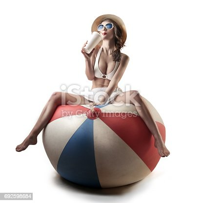 Woman is sitting on a huge ball, while drinkig some refreshment