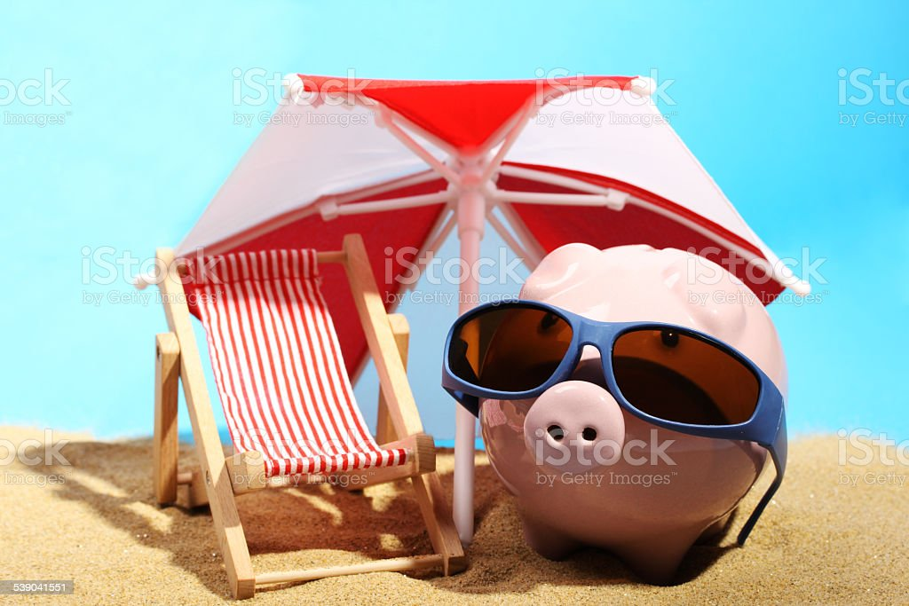 Summer piggy bank with heart sunglasses standing on sand stock photo