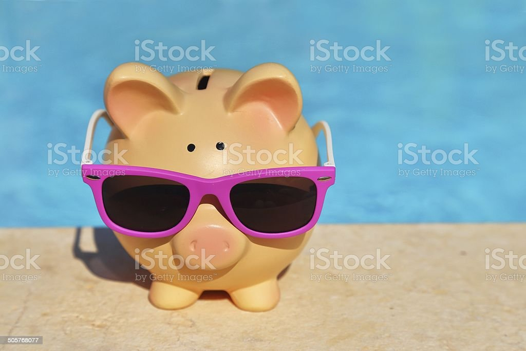 Summer piggy bank with sunglasses stock photo