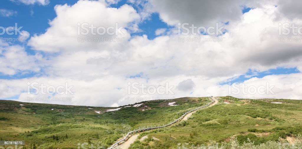 Summer Pipeline Climbing Hill With Dramatic Summer Sky stock photo