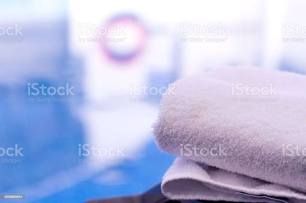 Summer pool background with closeup of a white towel stock photo