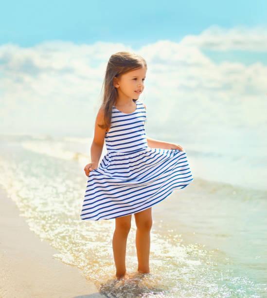 Summer portrait beautiful little girl child in striped dress walking on beach near sea with waves stock photo