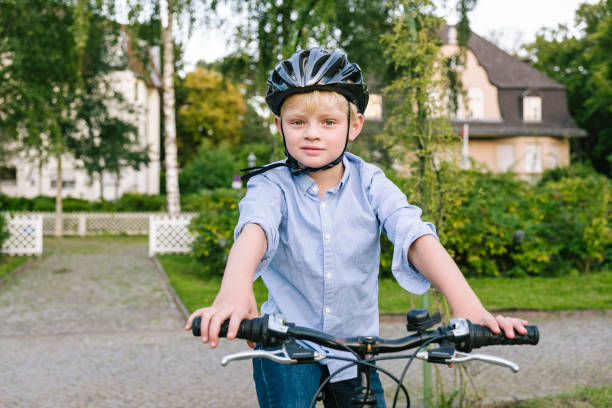 summer portrait of a boy wearing cycling helmet in a park stock photo
