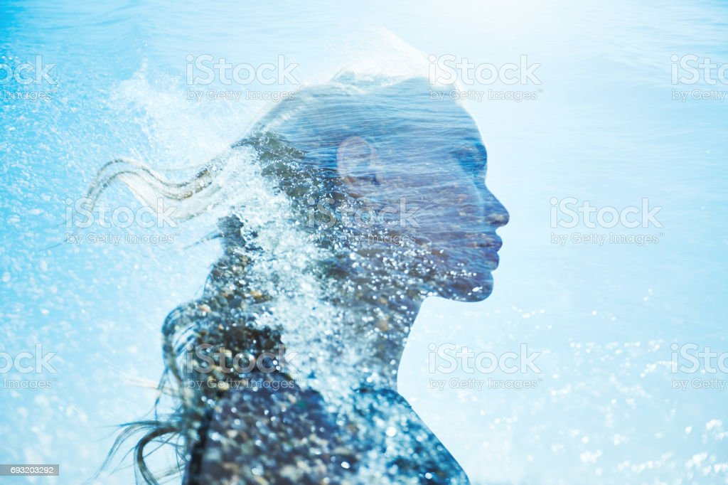 Summer portrait of a girl in blue sea waves. Beautiful blonde on the background of the sea, summer vacation at sea. A mysterious girl in sea foam stock photo