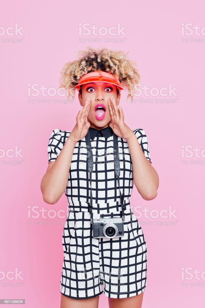 Summer portrait of afro american woman shouting Studio portrait of excitedafro american young woman shouting at the camera. Pink background. 20-24 Years Stock Photo