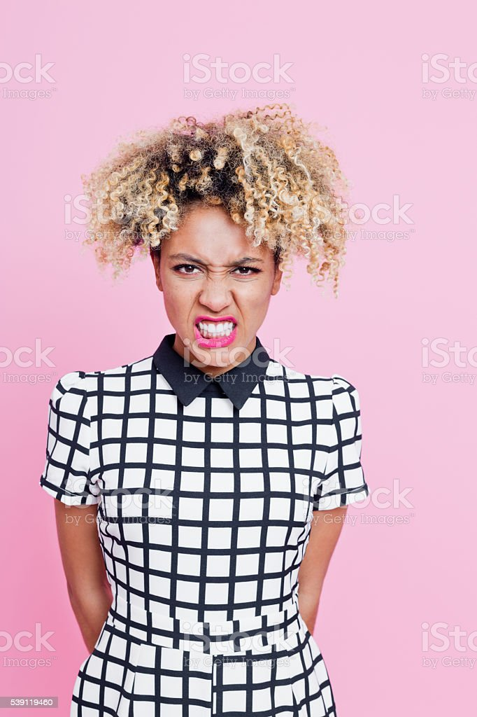 Summer portrait of angry afro american woman Summer portrait of angry afro american young man wearing headphone, cap and jeans sleeveless jacket, standing against pink background, staring at camera. 25-29 Years Stock Photo