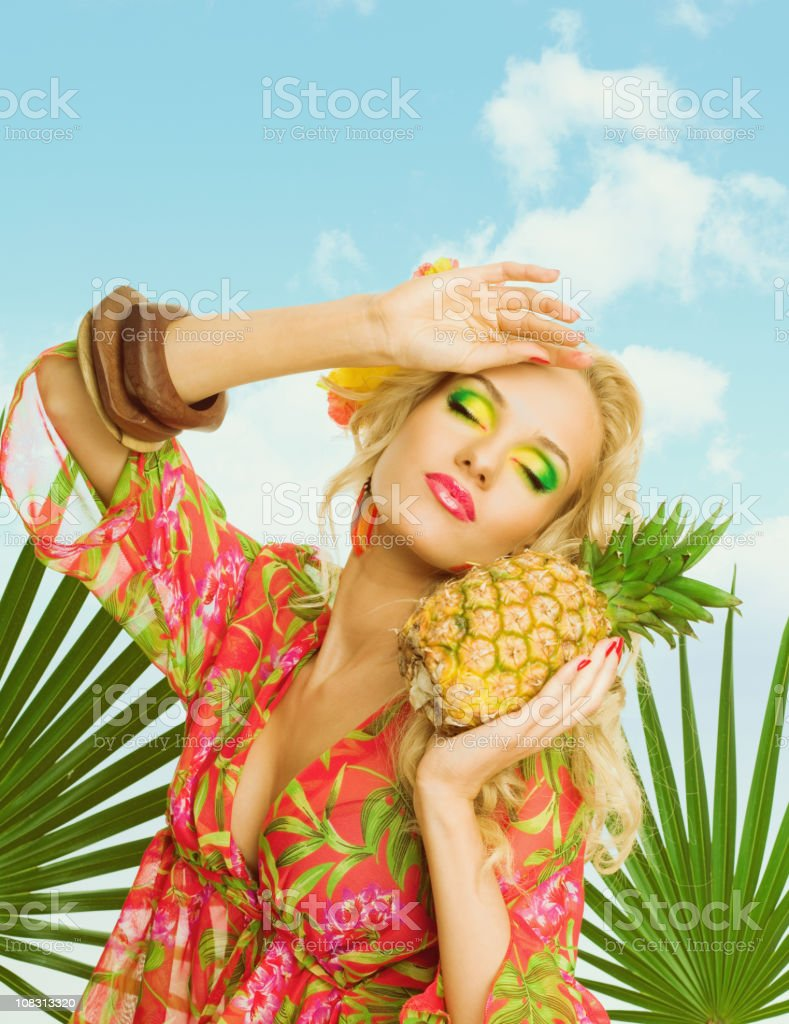 Summer portrait of attractive blonde woman holding pineapple fruit Summer portrait of a beautiful blonde woman wearing a colorful tunic and holding pineapple fruit. 20-24 Years Stock Photo