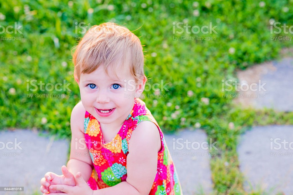 Summer portrait of beautiful baby girl on the lawn stock photo