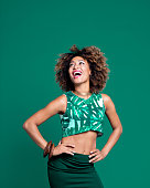 Summer portrait of excited afro american young woman wearing palm leaf pattern top. Studio shot, green background.
