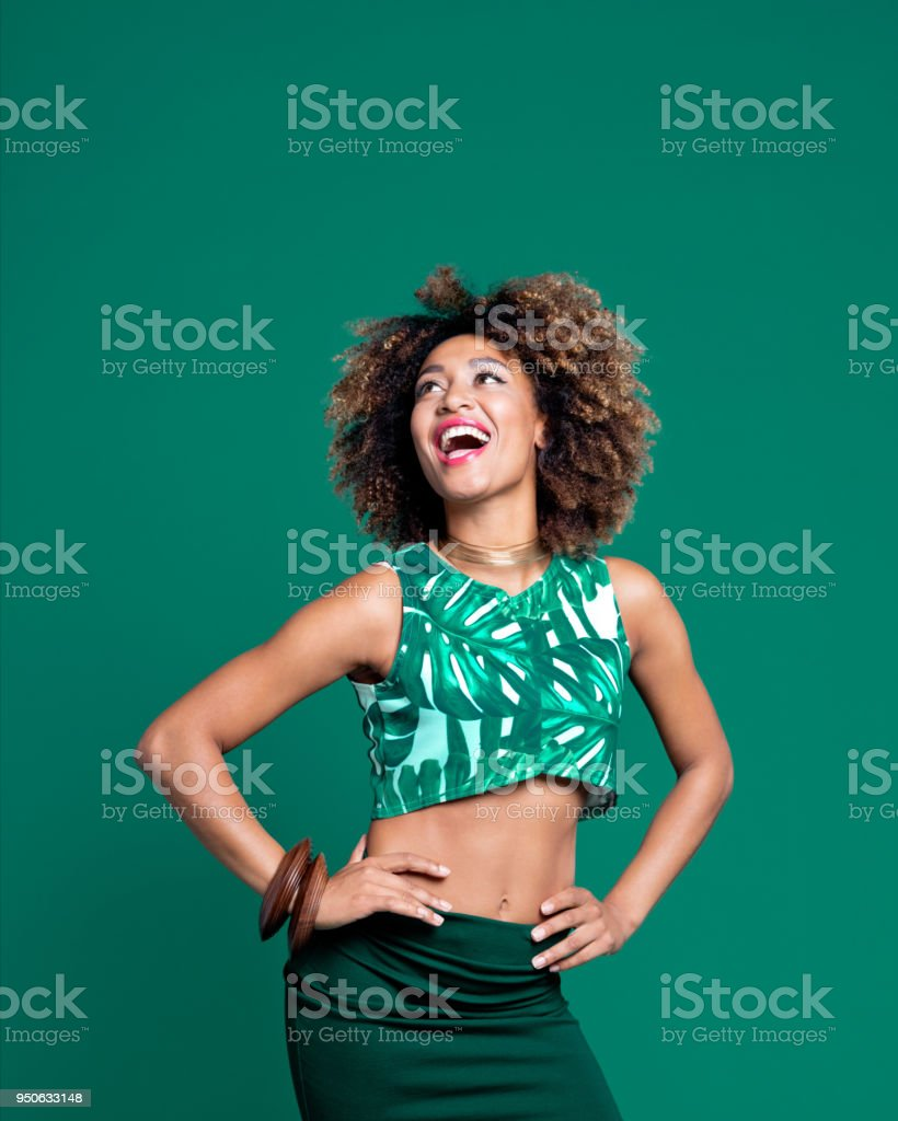 Summer portrait of excited afro young woman against green background stock photo