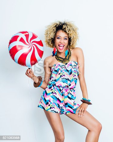 521083232istockphoto Summer portrait of excited afro young woman with balloon 521083568