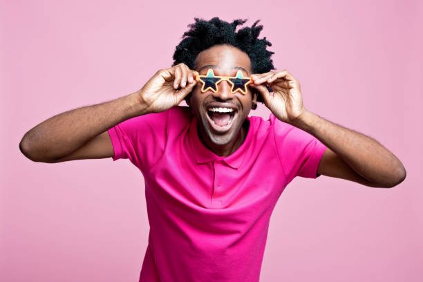 Summer portrait of excited young man wearing star shaped sunglasses stock photo