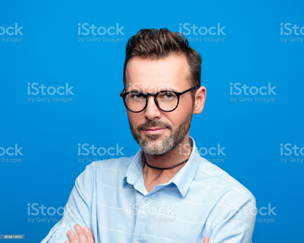 Summer portrait of handsome man, blue background Summer portrait of handsome man wearing blue shirt and glasses. Studio shot, blue background. 30-39 Years Stock Photo