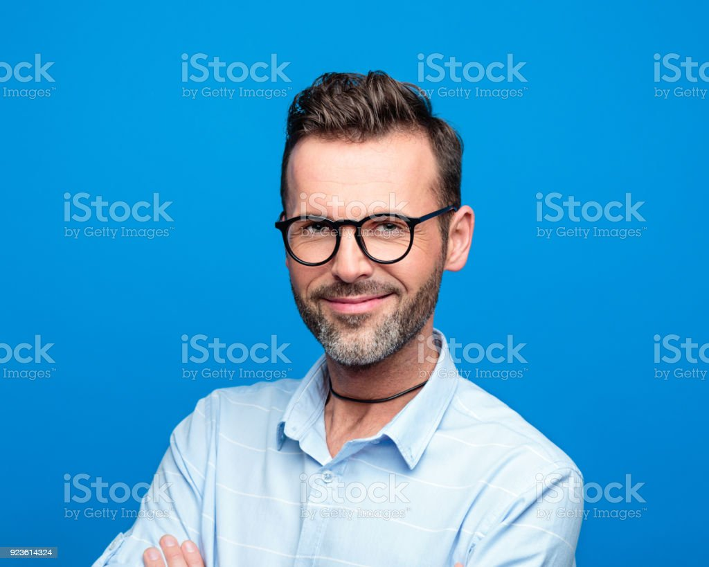 Summer portrait of handsome smiling man, blue background Summer portrait of handsome man wearing blue shirt and glasses. Studio shot, blue background. 30-39 Years Stock Photo