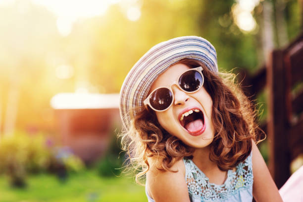 summer portrait of happy kid girl on vacation in sunglasses and hat, laugh and showing tongue. stock photo
