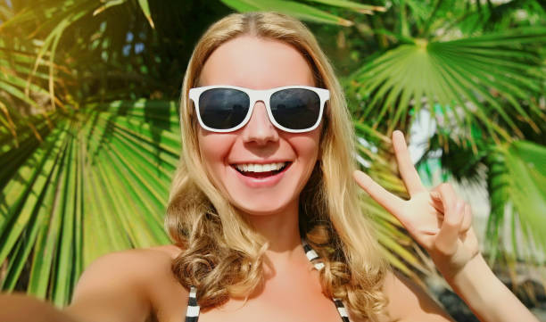 Summer portrait of happy smiling young woman stretching her hand for taking selfie picture by smartphone on a beach, palm tree background stock photo