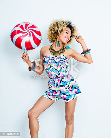 521083232istockphoto Summer portrait of sensual afro young woman with balloon 521083596