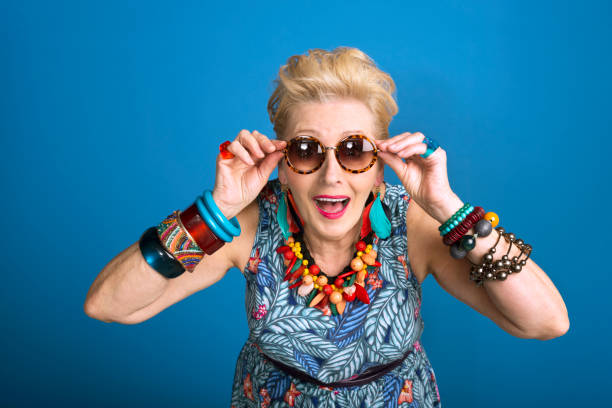 Summer portrait of young at heart senior woman Summer portrait of creative, colorful senior woman against blue background. Studio shot. young at heart stock pictures, royalty-free photos & images