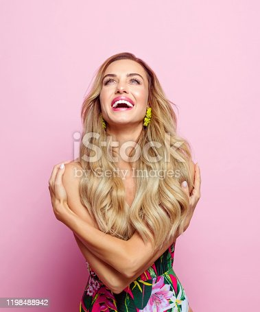 Glamour portrait of beautiful long hair young woman wearing elegant floral swimsuit. Studio shot on pink background.