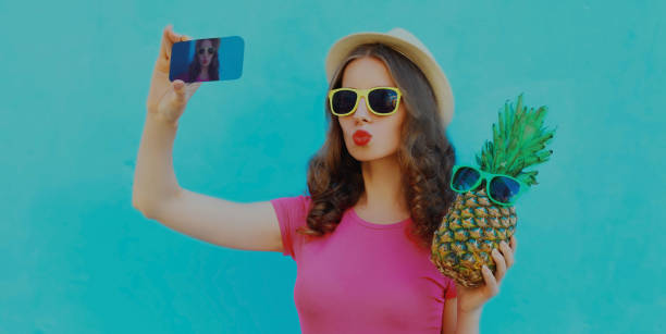Summer portrait of young woman taking selfie picture by phone with pineapple wearing a sunglasses on a blue background stock photo