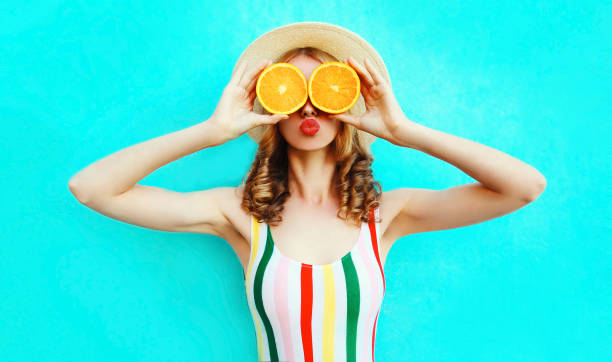 Summer portrait woman holding in her hands two slices of orange fruit hiding her eyes in straw hat on colorful blue background stock photo